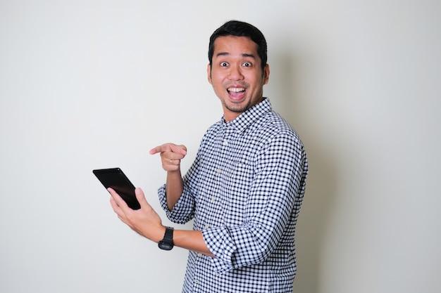 행복한 얼굴 표정으로 모바일 태블릿을 가리키는 성인 아시아 남자
