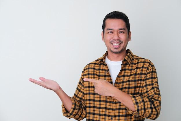 笑顔で彼の手の手のひらを指している大人のアジア人男性