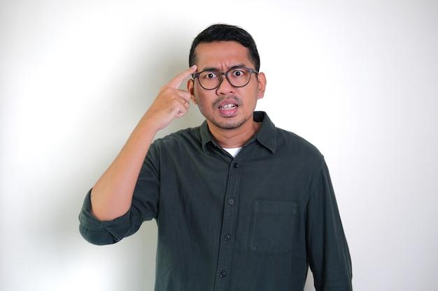 Взрослый азиатский мужчина показывает сердитое выражение с пальцем, указывающим на боковой лоб