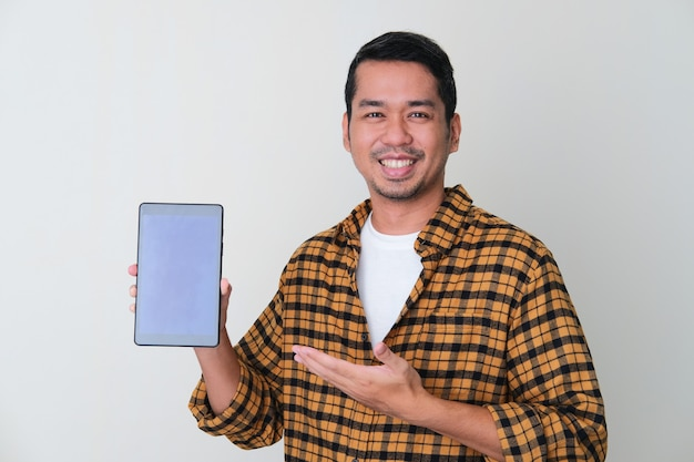 笑顔で空白のモバイルタブレット画面を示す大人のアジア人男性