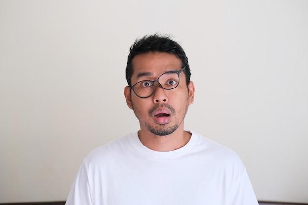 재미 있는 엉망 얼굴을 보여주는 성인 아시아 남자