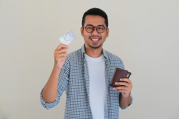 Adult asian man showing happy face expression while showing his credit card amd holding wallet