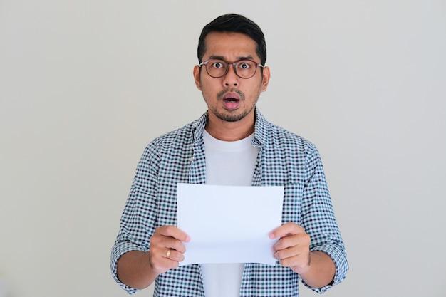 メッセージを読んだ後、ショックを受けた顔の表情を示す大人のアジア人男性