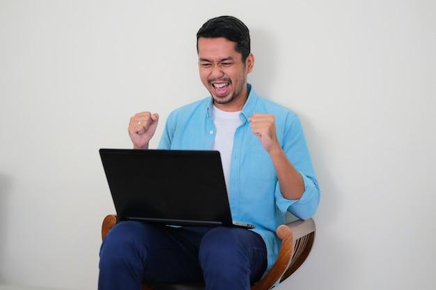 彼のラップトップコンピューターを見て勝利のジェスチャーを示す大人のアジア人男性