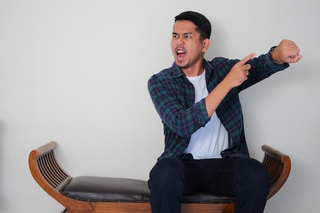 椅子に座って、腕の時計を指差しながら怒った表情を見せている大人のアジア人男性