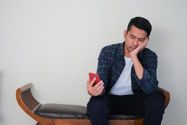 Взрослый азиатский мужчина сидит в кресле и показывает скучный жест, глядя на свой мобильный телефон
