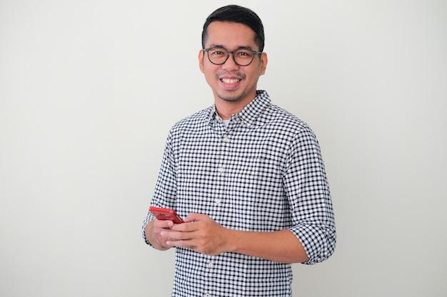 Взрослый азиатский мужчина уверенно улыбается, держа свой мобильный телефон