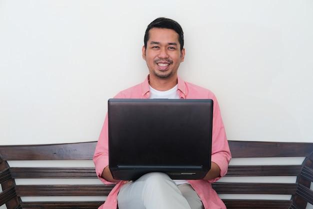 소파에 앉아 노트북을 사용하여 자신감 있게 웃고 있는 성인 아시아 남자