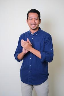 다른 사람에게 박수를 보낼 때 행복하게 웃고 있는 성인 아시아 남자
