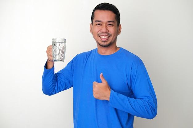 미네랄 워터 한 잔을 들고 행복하게 웃고 있는 성인 아시아 남자