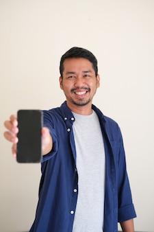 Взрослый азиатский мужчина улыбается счастливым, показывая пустой экран мобильного телефона