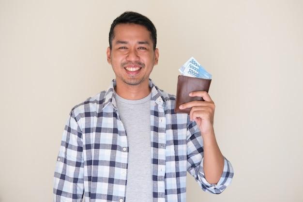 지폐로 가득 찬 지갑을 보여주며 행복한 미소를 짓고 있는 성인 아시아 남자