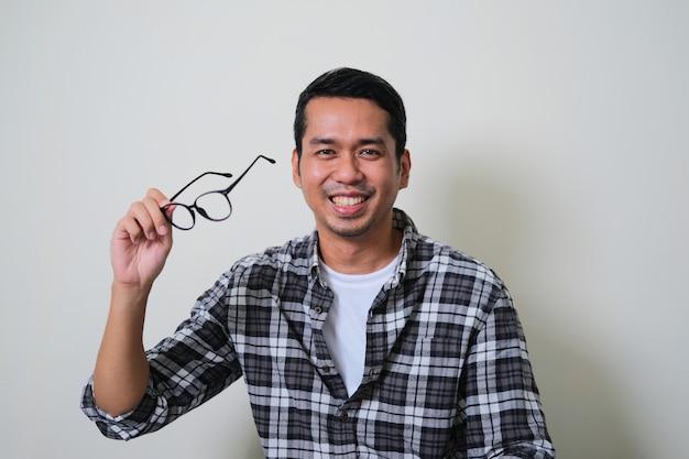 안경을 벗으면서 행복한 미소를 짓고 있는 성인 아시아 남자