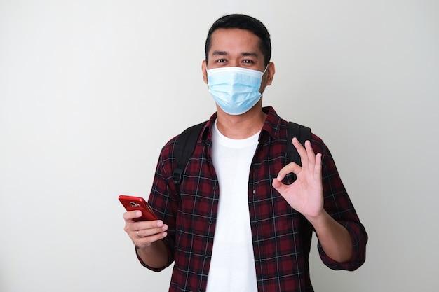 携帯電話を保持しながらok指サインを与える保護医療マスクを身に着けている大人のアジア人男性