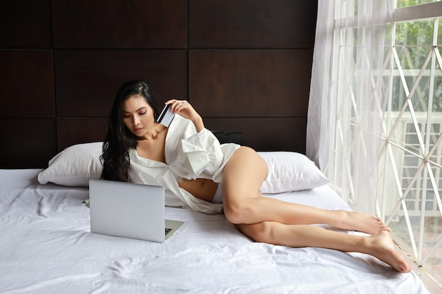 Adult asian sexy woman wearing white dress shopping online on computer with credit card while lying on bed in bedroom