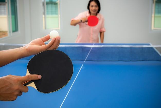 성인 아시아 여성이 실내에서 탁구나 탁구를 시작하기 위해 기다리고 있습니다. 집에서 스포츠 게임을 하며 여가를 즐기거나 태국에서 가족과 함께 집에서 여가 또는 운동