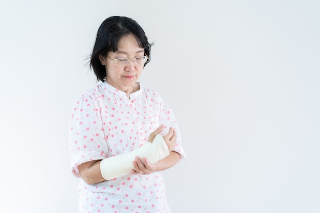 Adult asian woman broken arm from accident, close up in half body with copy space.  concept of healthcare and aging society.
