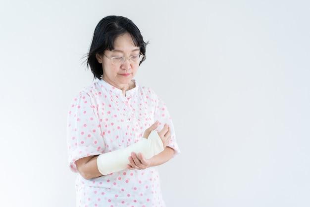 事故から腕を骨折した大人のアジアの女性は、コピースペースと半身でクローズアップ。ヘルスケアと高齢化社会の概念。