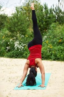 Взрослая азиатская женщина занимается йогой на природе, делает упражнения на растяжку и гибкость, занятия йогой для взрослых женщин