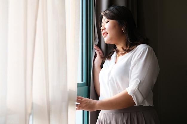 창밖을 내다보며 행복한 미소를 짓고 있는 성인 아시아 여성