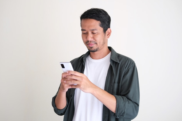 Взрослый азиатский молодой человек смотрит на свой мобильный телефон