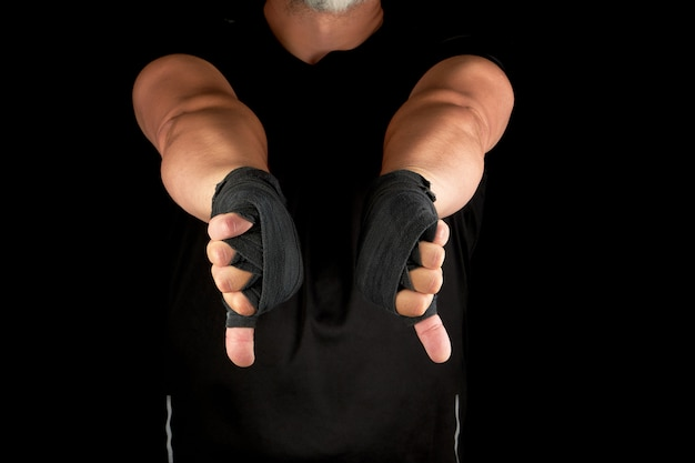 Adult athlete in black uniform and hands rewound with textile bandage