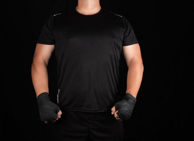 Adult athlete in black uniform is standing in a rack with strained muscles