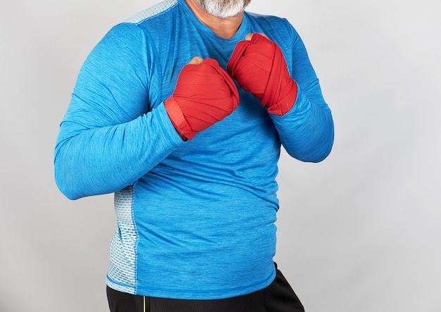 Adult athlete in blue clothes, hands wrapped in a red elastic bandage