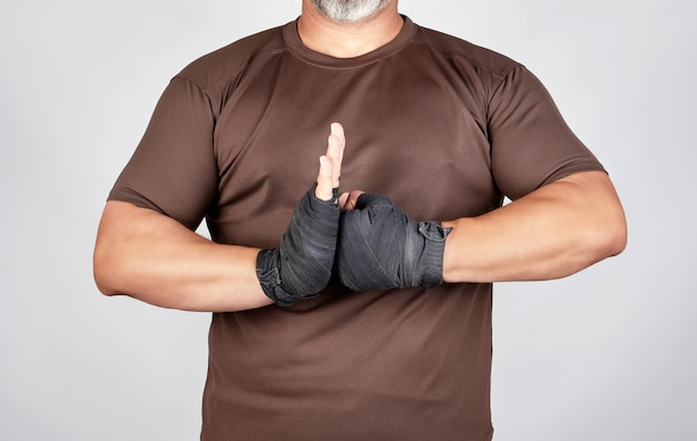 Adult athlete in brown clothes with bandaged hands black textile sports bandage