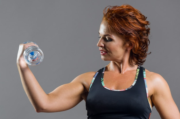 Adult athletic fitness red-haired woman in sports uniform with a bottle of water