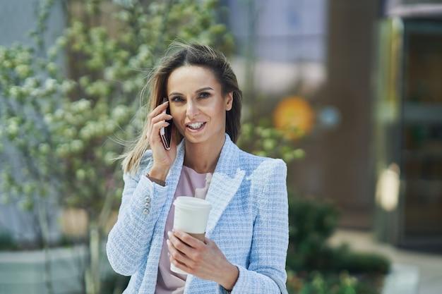 Взрослый привлекательный бизнес-леди с смартфон и кофе, идущий по городу. фото высокого качества