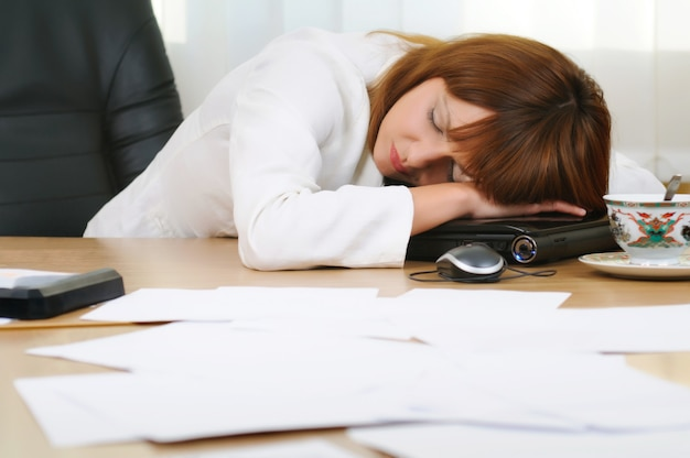 Adult attractive caucasian white brunette businesswoman sleeping or taking a nap at her laptop, tired female accountant with paper folders in office.