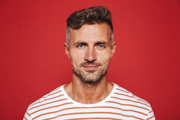 Взрослый привлекательный мужчина с щетиной в полосатой футболке улыбается изолированно на красном
