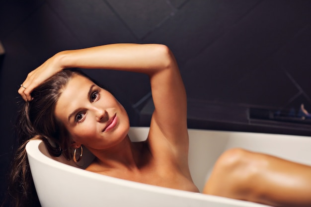 Adult attractive woman relaxing in bath tube with fireplace in background