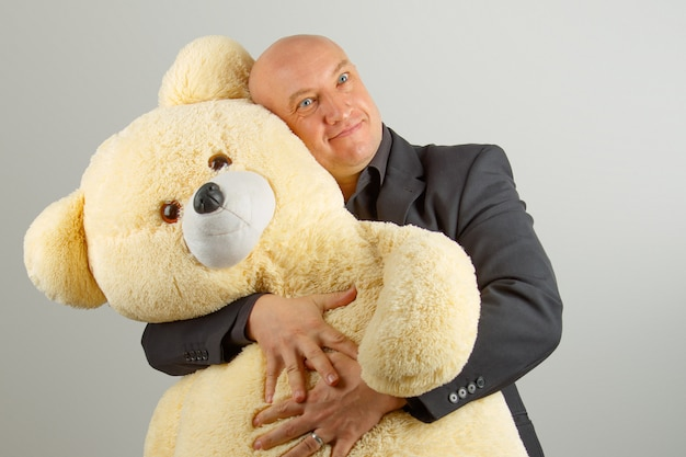 An adult bald man in a black suit holds a large toy bear on a gray