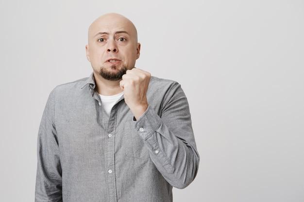 Adult bald man scolding with raised fist, threatening