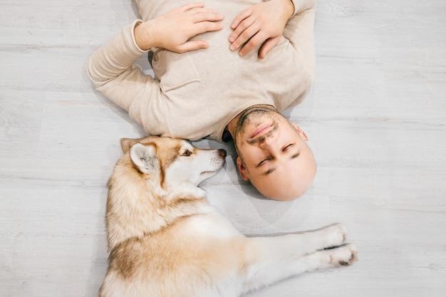 床で寝ているハスキーの子犬と大人のハゲ男。家で一緒にペットを持つ所有者。若い男性と一緒に休んでいる素敵な犬。お互いを抱いて愛する家畜を持つ男。