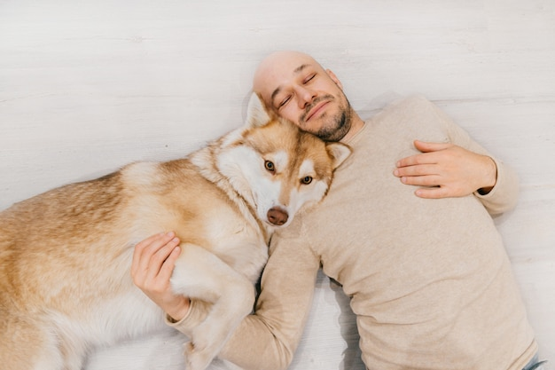 床で寝ているハスキーの子犬と大人のハゲ男。自宅で一緒にペットを持つ所有者。