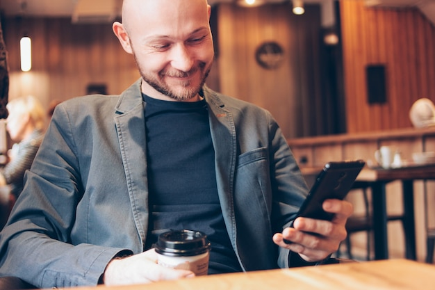 Adult bald smiling man drinking coffee from paper cup and using mobile phone at cafe