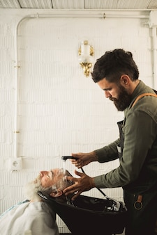 Adult barber washing old man hair on backwash