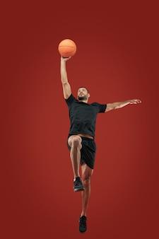 Взрослый бородатый мужчина в черной спортивной одежде играет в баскетбол в спортивном центре