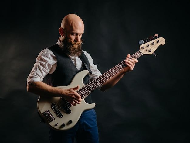 黒で熱狂的にギターを弾く大人のひげを生やした男