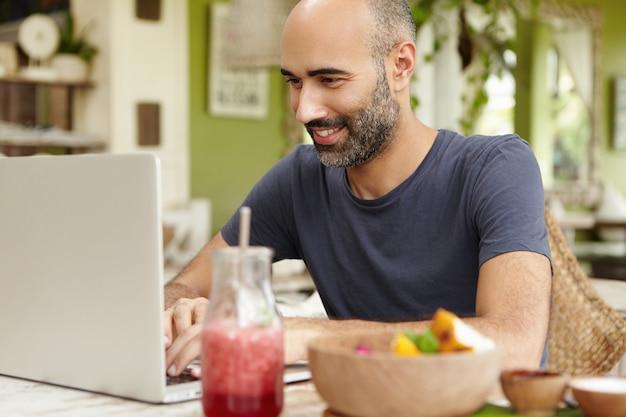 大人のひげを生やした男がカフェで朝食をとり、汎用のラップトップの前のテーブルに座って、ソーシャルネットワーク経由で友達にメッセージを送りながら笑顔で見て、無料のwi-fiを楽しんでいます。