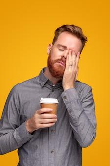 睡眠不足に苦しんで目をこすり、黄色の背景に行くためにコーヒーを飲む灰色のシャツの大人のひげを生やした男
