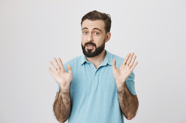 Adult bearded man talking and showing empty hands
