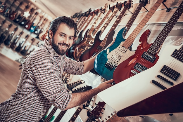 Adult bearded musician buys electric guitar in music store.