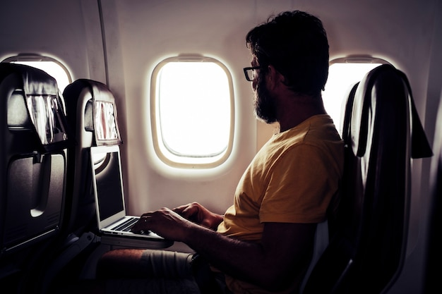 Adult bearded traveler man sitting inside the aircraft and flight to destination