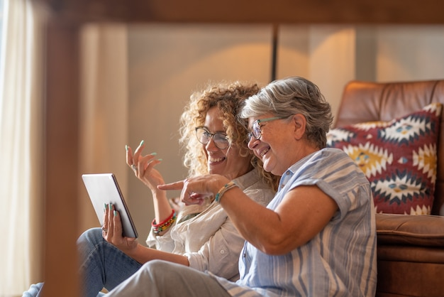 Adult beautiful daughter with elderly mother sitting at home looking social media on digital tablet