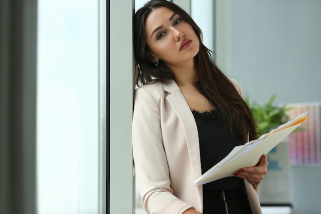 Взрослый красивая счастливая улыбка модная бизнес-леди клиент индийский занятый поставщик практики управления стоя на рабочем месте офиса. держите в руках папку со статистической рассылкой черновиков