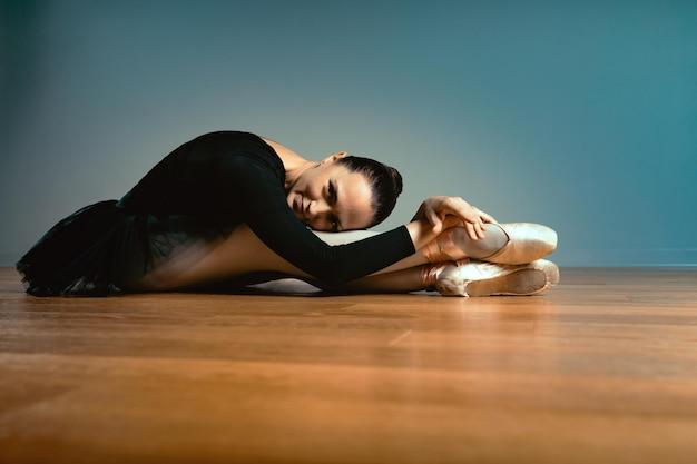 45〜55歳の大人の美しい女性、トウシューズのバレリーナは床に座ってカメラのポーズをとります。アクティブな老後、人生の知識。昔ながらのバレエトレーナー。